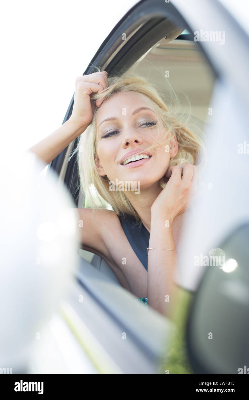 Happy young woman leaning on car window - Stock Image