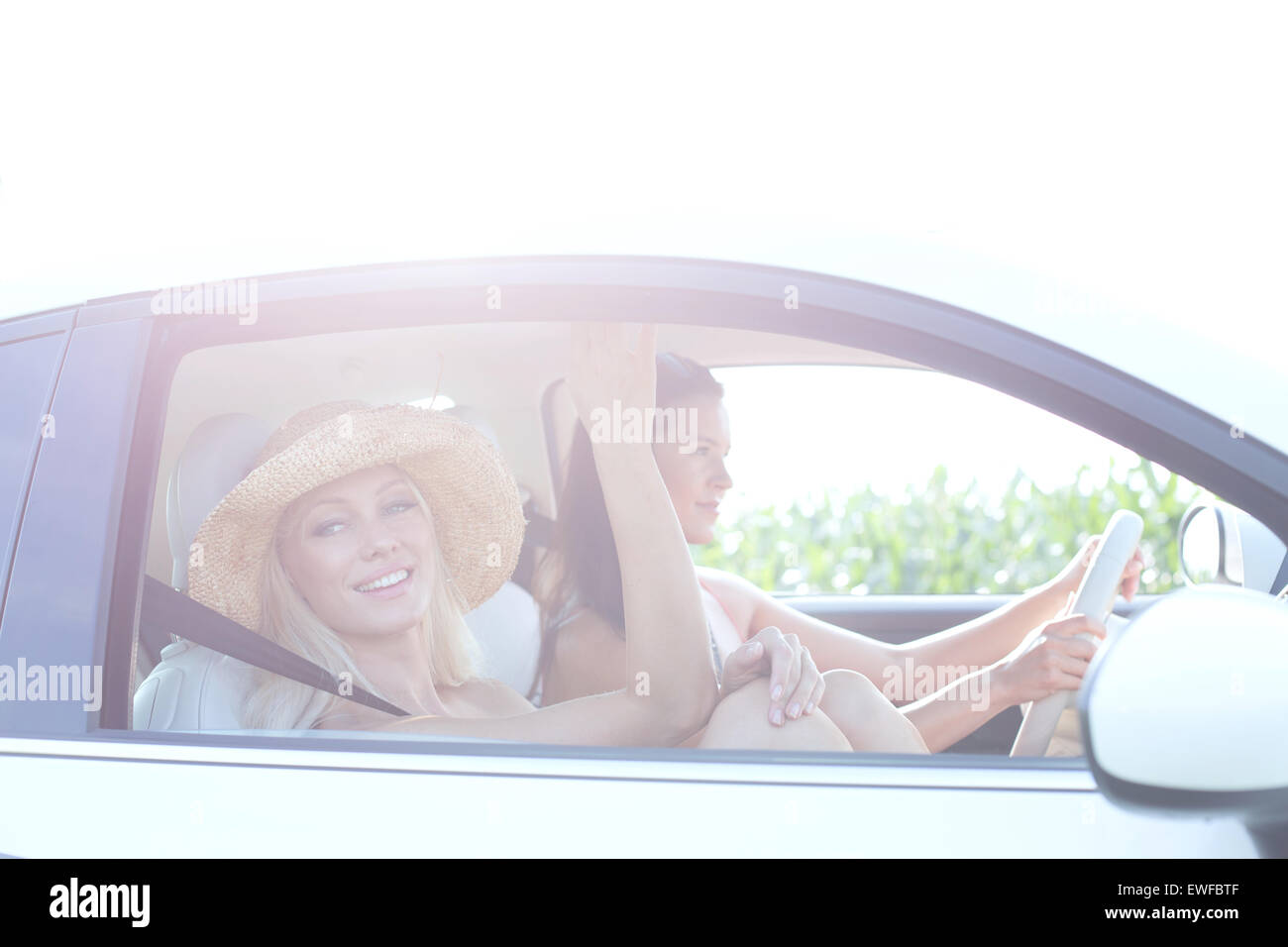 Happy women enjoying road trip on sunny day - Stock Image