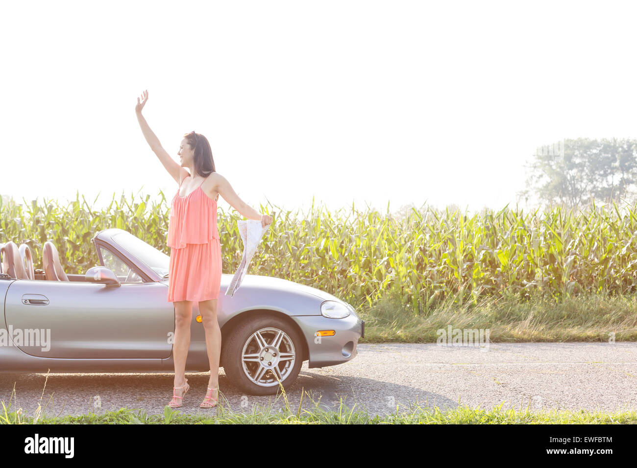 Full length of woman gesturing while holding map by convertible against clear sky - Stock Image