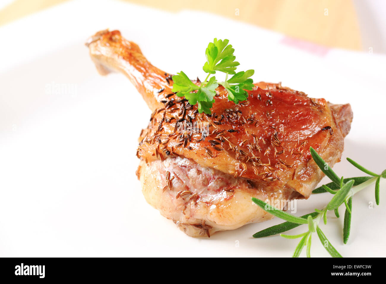 Roast duck leg topped with caraway seeds - Stock Image