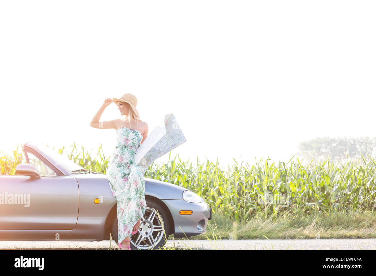 Happy woman holding map while standing by convertible on sunny day - Stock Image