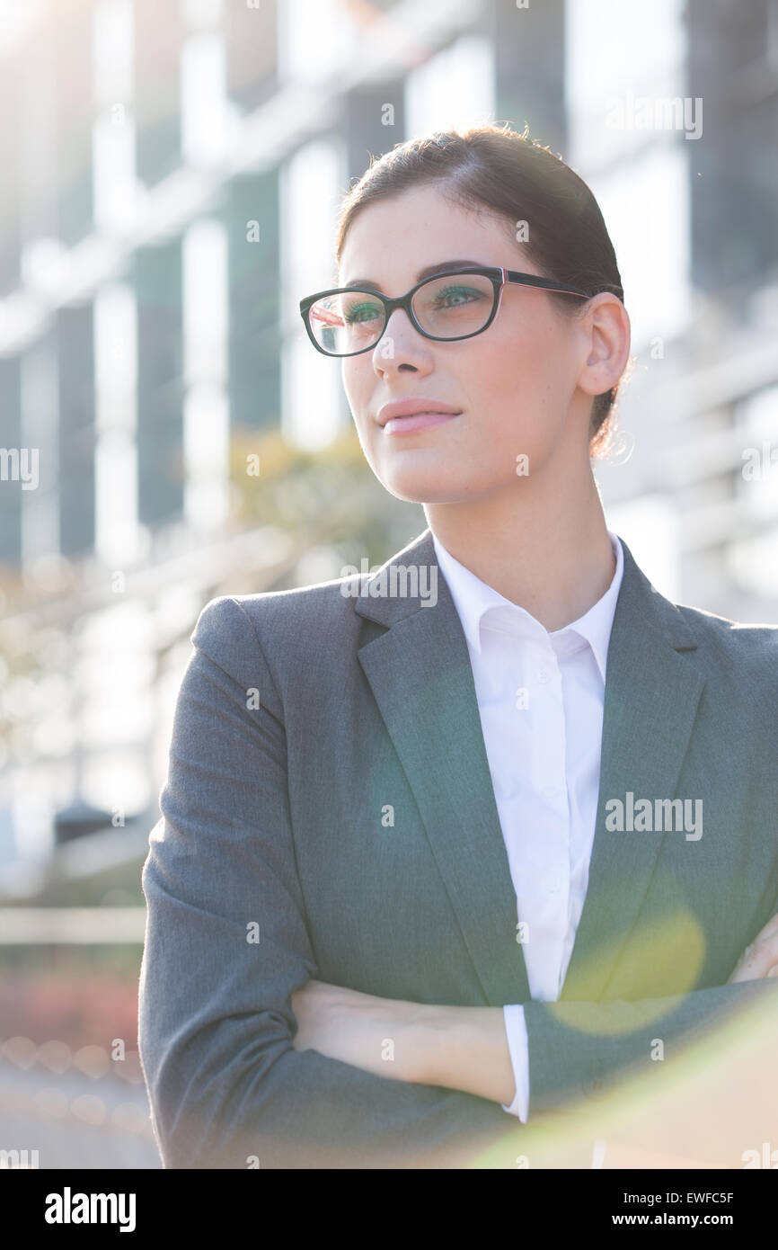 Thoughtful businesswoman standing arms crossed outdoors - Stock Image