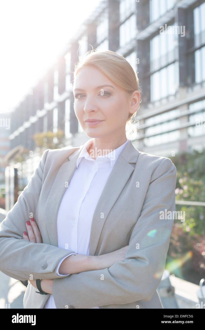 Portrait of confident businesswoman standing arms crossed outside office building - Stock Image