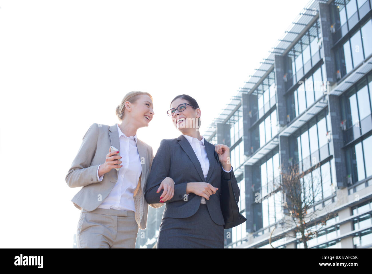 Low angle view of happy businesswomen walking outside office building against clear sky - Stock Image