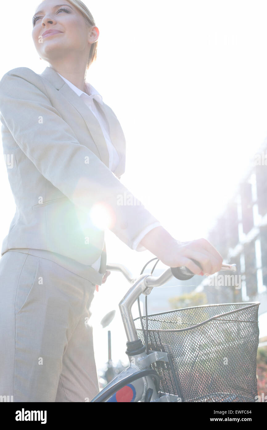 Low angle view of businesswoman standing with bicycle on sunny day Stock Photo