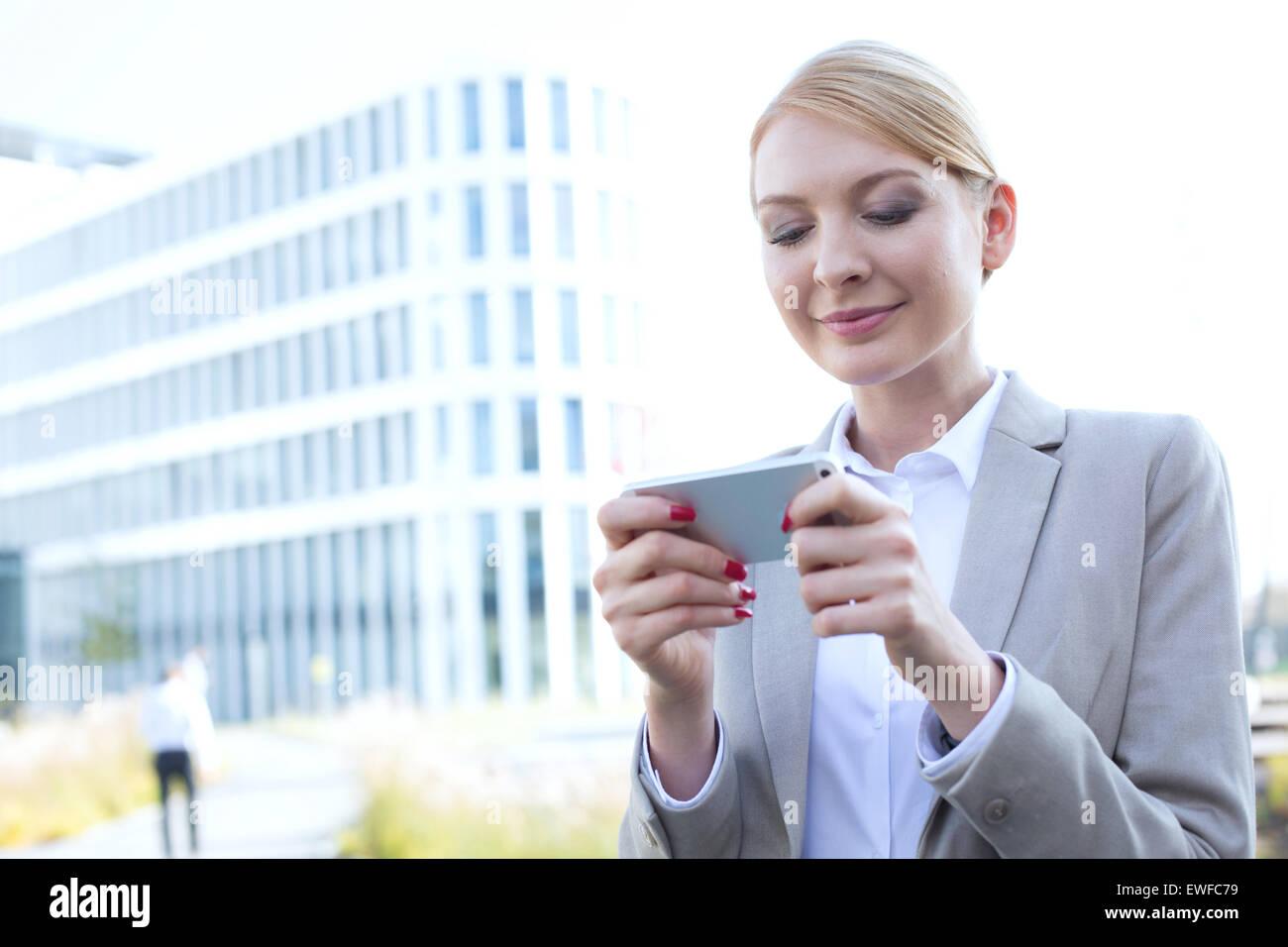Businesswoman text messaging through smart phone outdoors - Stock Image
