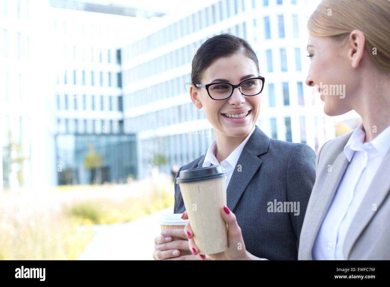 Happy businesswomen conversing while holding disposable cups outdoors - Stock Image