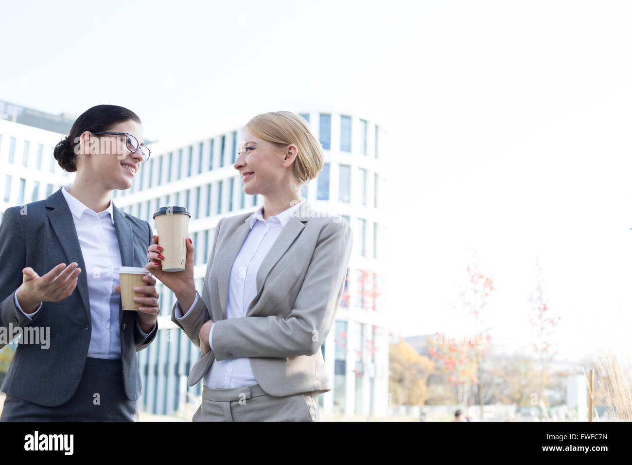 Happy businesswomen conversing while holding disposable cups outside office building - Stock Image