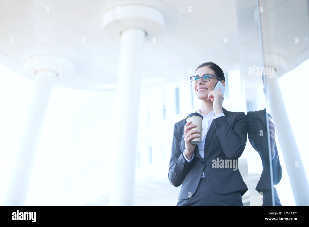 Businesswoman using cell phone while holding disposable cup outdoors - Stock Image