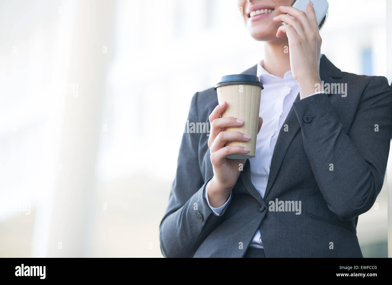 Midsection of businesswoman using cell phone while holding disposable cup outdoors - Stock Image