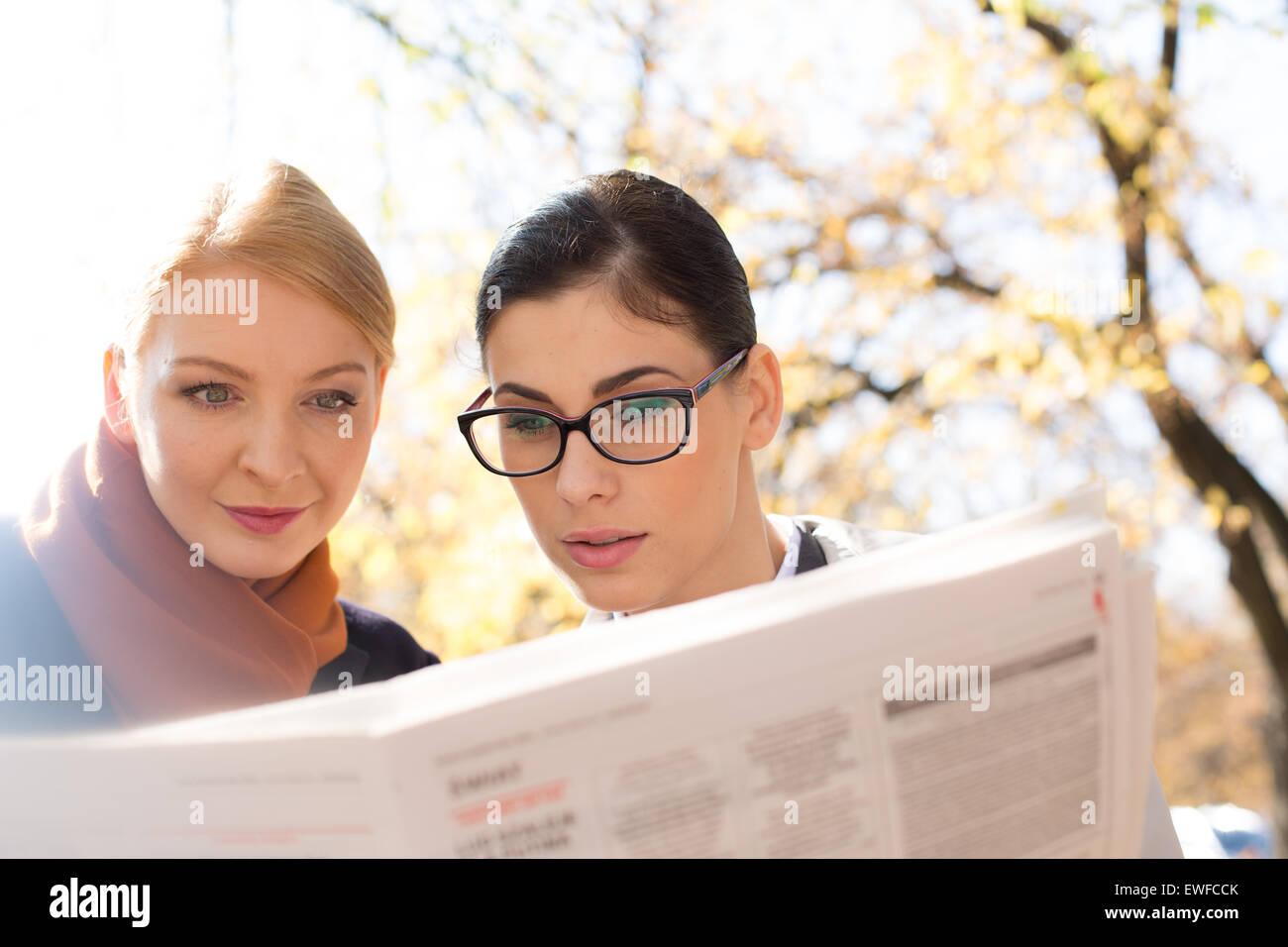 Businesswomen reading newspaper at park - Stock Image