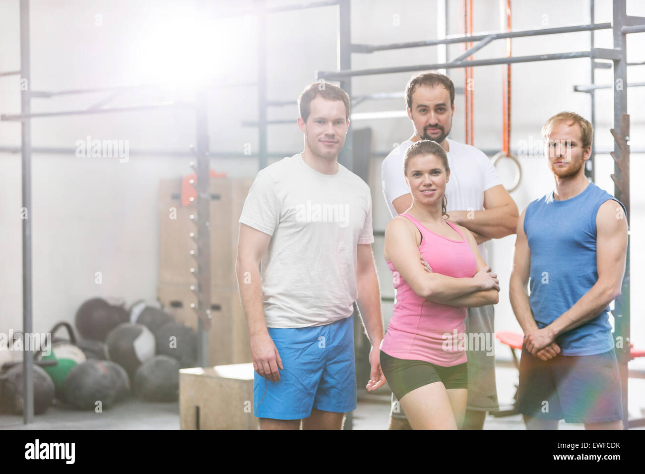 Portrait of confident men and women standing at crossfit gym - Stock Image