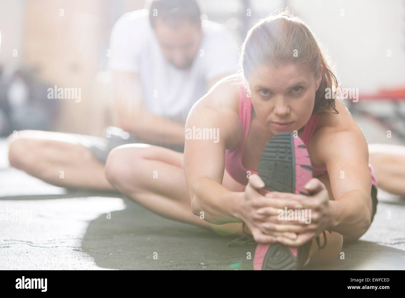 Portrait of confident woman doing stretching exercise in crossfit gym - Stock Image