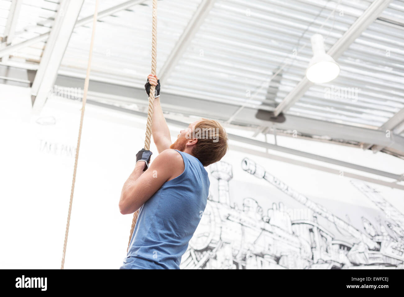 Side view of dedicated man climbing rope in crossfit gym - Stock Image