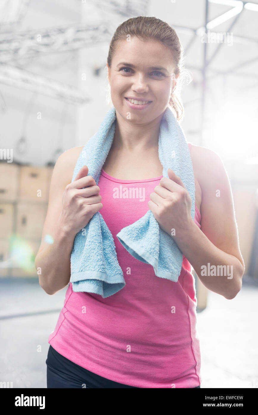 Portrait of happy woman with towel around neck standing in crossfit gym - Stock Image