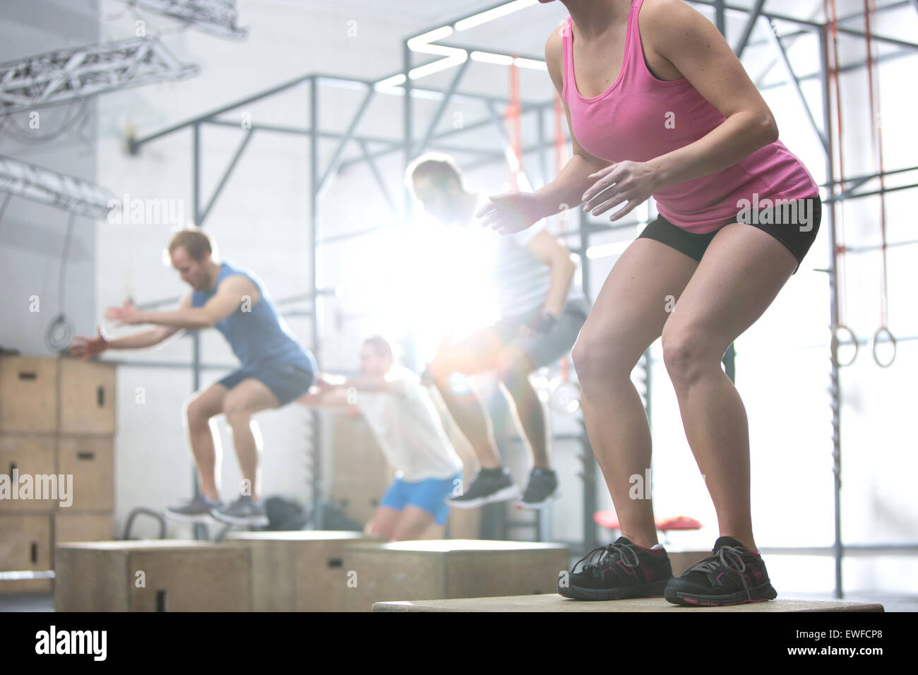People doing box jump exercise in crossfit gym - Stock Image