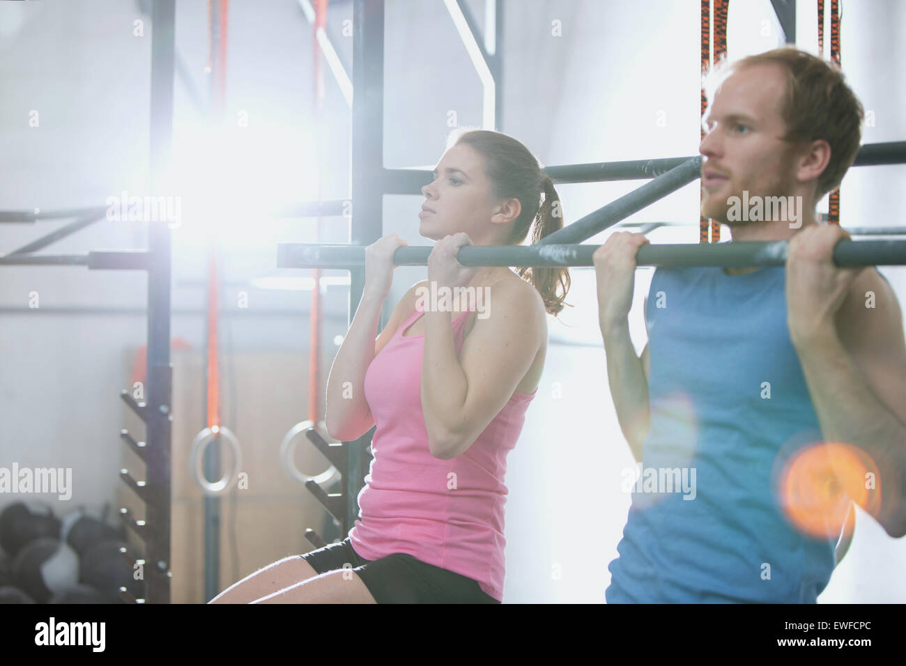 Man and woman doing pull ups in crossfit gym - Stock Image