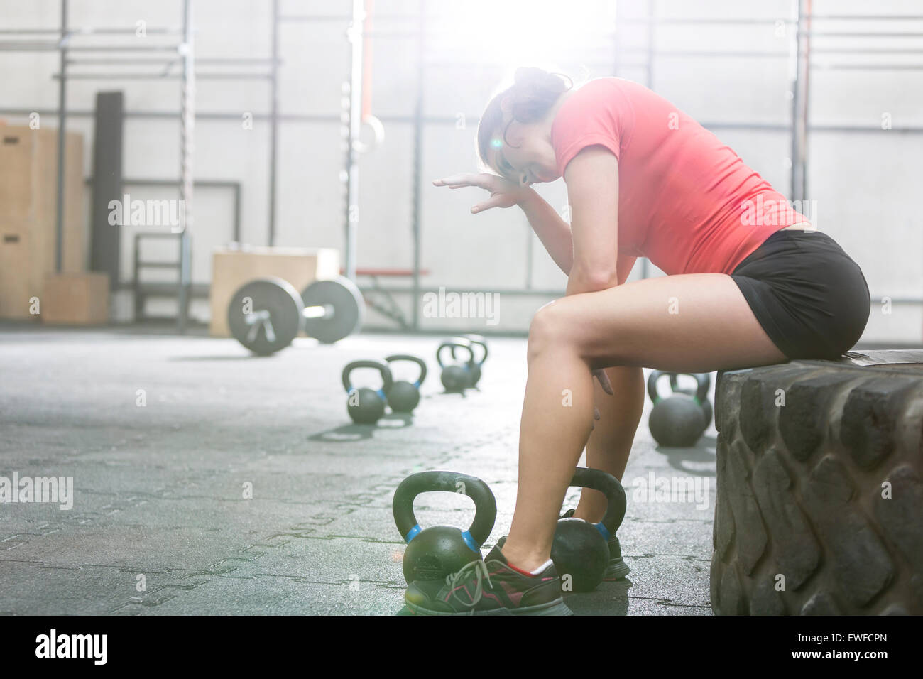 Exhausted woman sitting on tire in crossfit gym - Stock Image