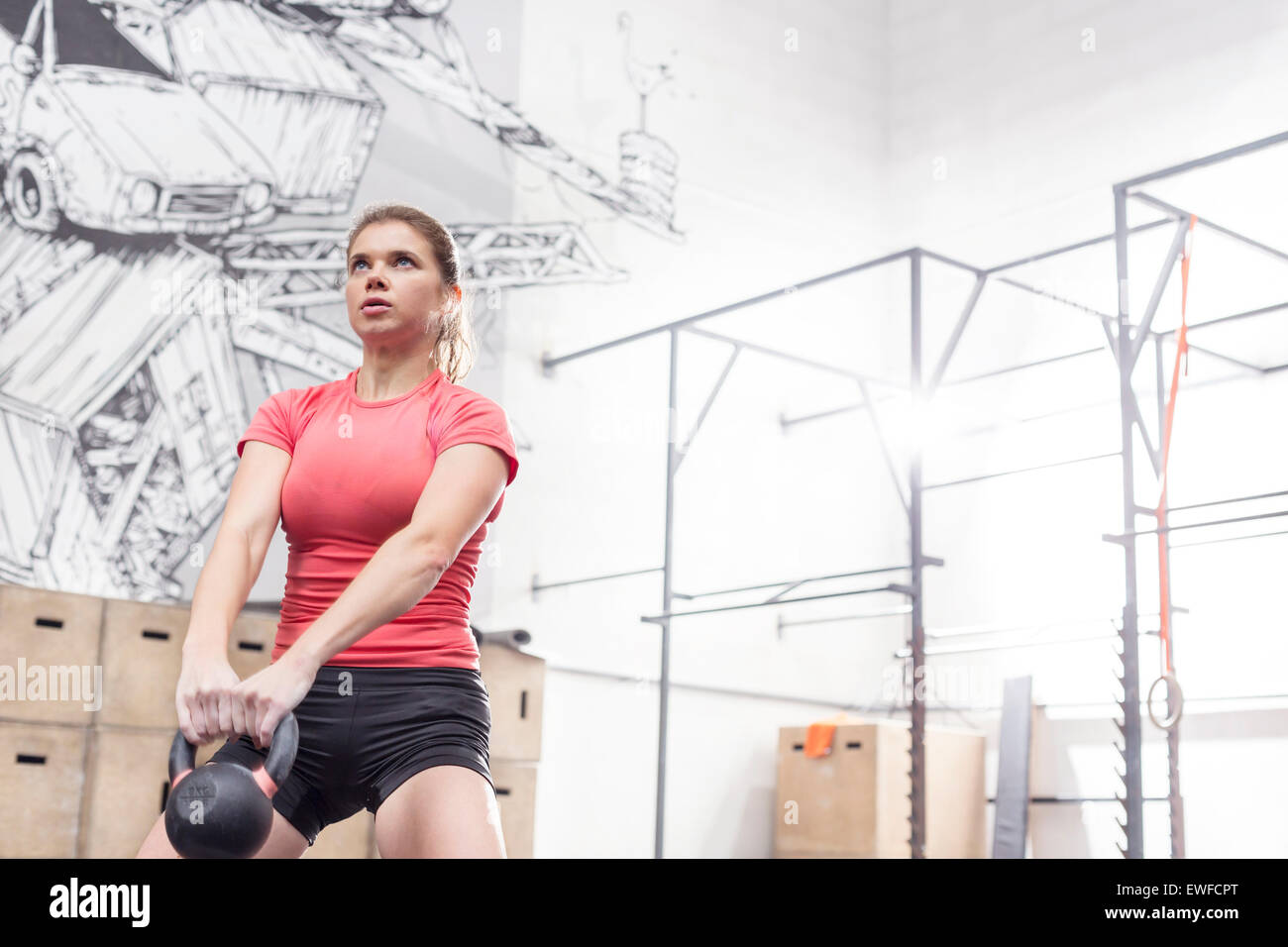 Dedicated woman lifting kettlebell in crossfit gym - Stock Image