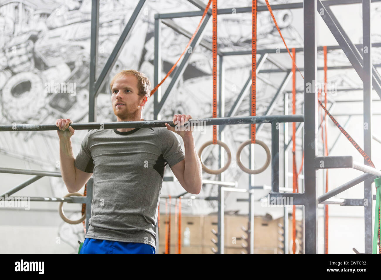 Confident man doing chin-ups in crossfit gym - Stock Image