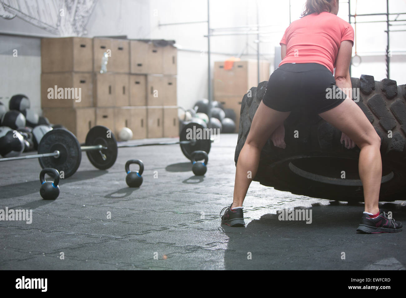 Rear view of woman flipping tire in crossfit gym - Stock Image