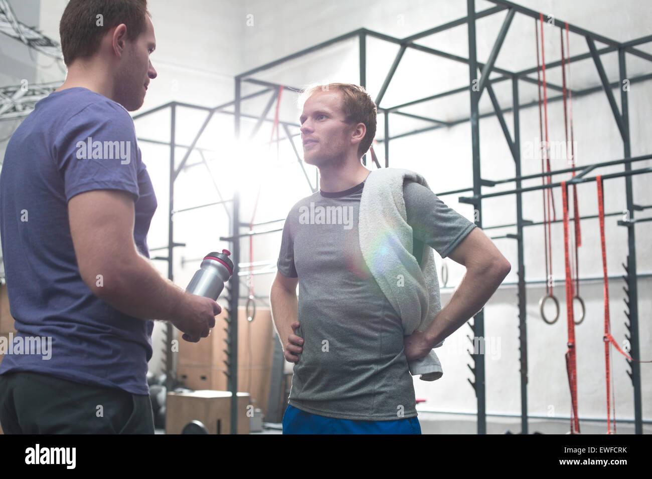 Male friends talking in crossfit gym - Stock Image