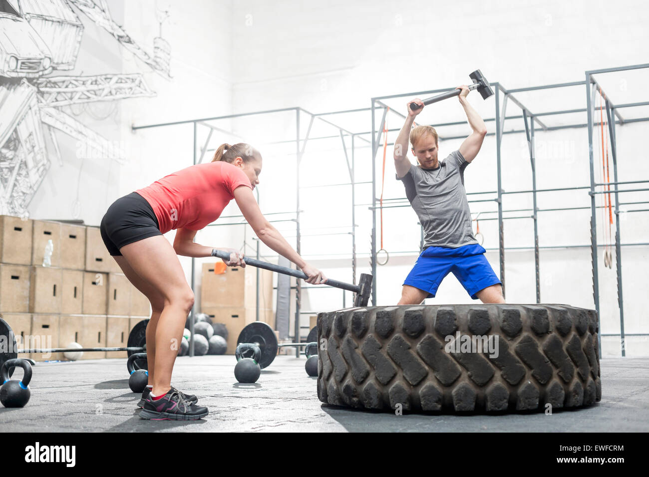 Man and woman hitting tire with sledgehammer in crossfit gym - Stock Image
