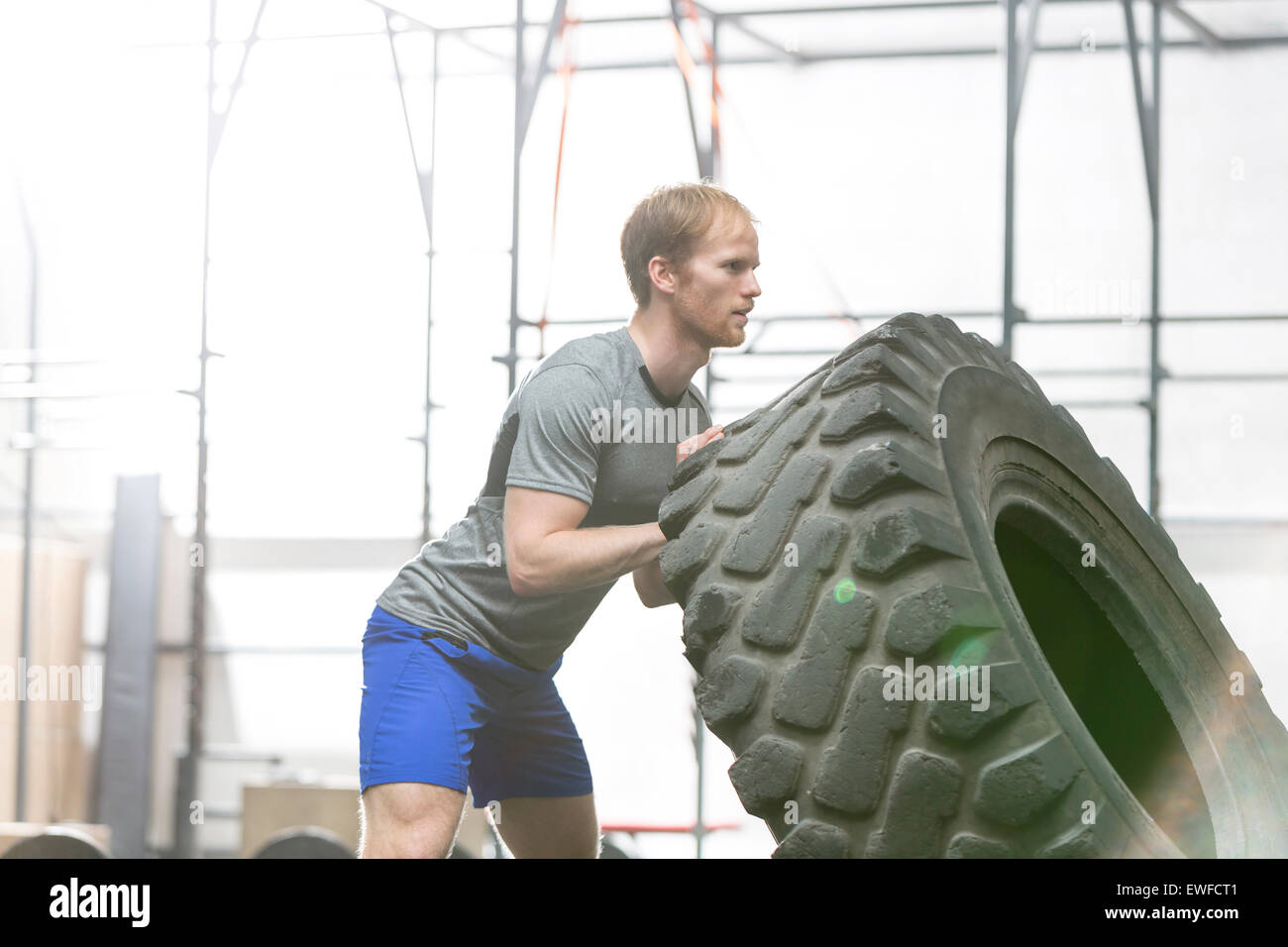 Side view of dedicated man flipping tire in crossfit gym - Stock Image