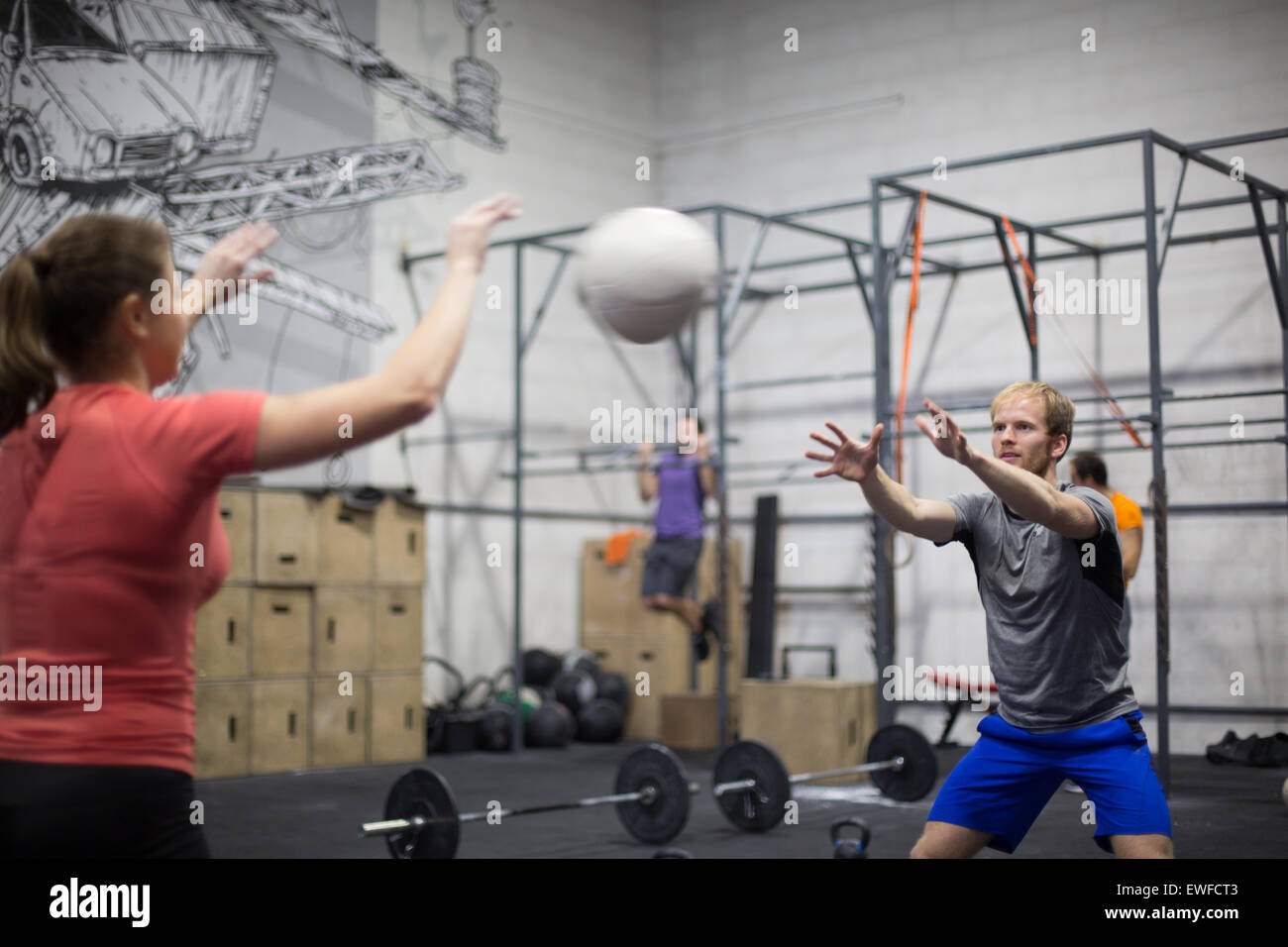 Man throwing medicine ball towards woman in crossfit gym - Stock Image