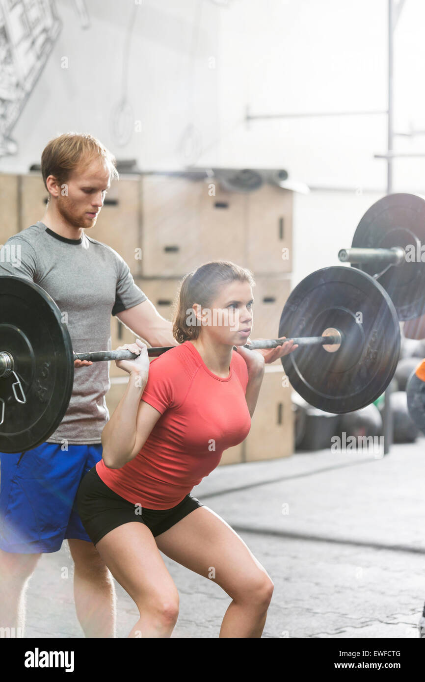 Man assisting woman in lifting barbell in crossfit gym - Stock Image