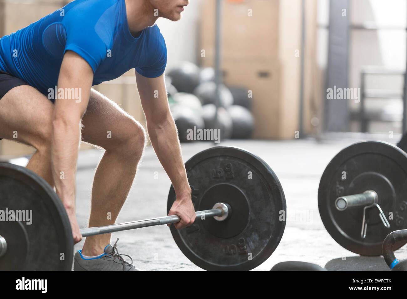 Low section of dedicated man lifting barbell in crossfit gym - Stock Image