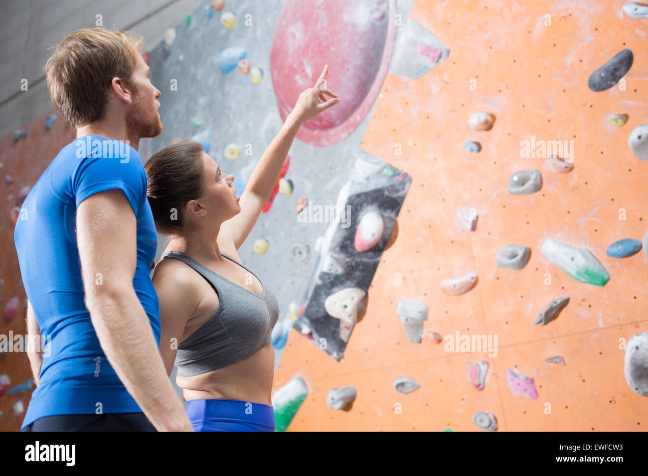 Friends discussing by climbing wall in crossfit gym - Stock Image