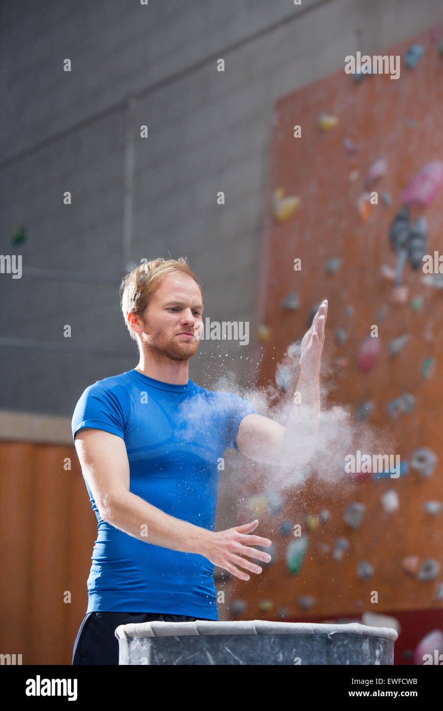 Man dusting powder by climbing wall in crossfit gym - Stock Image