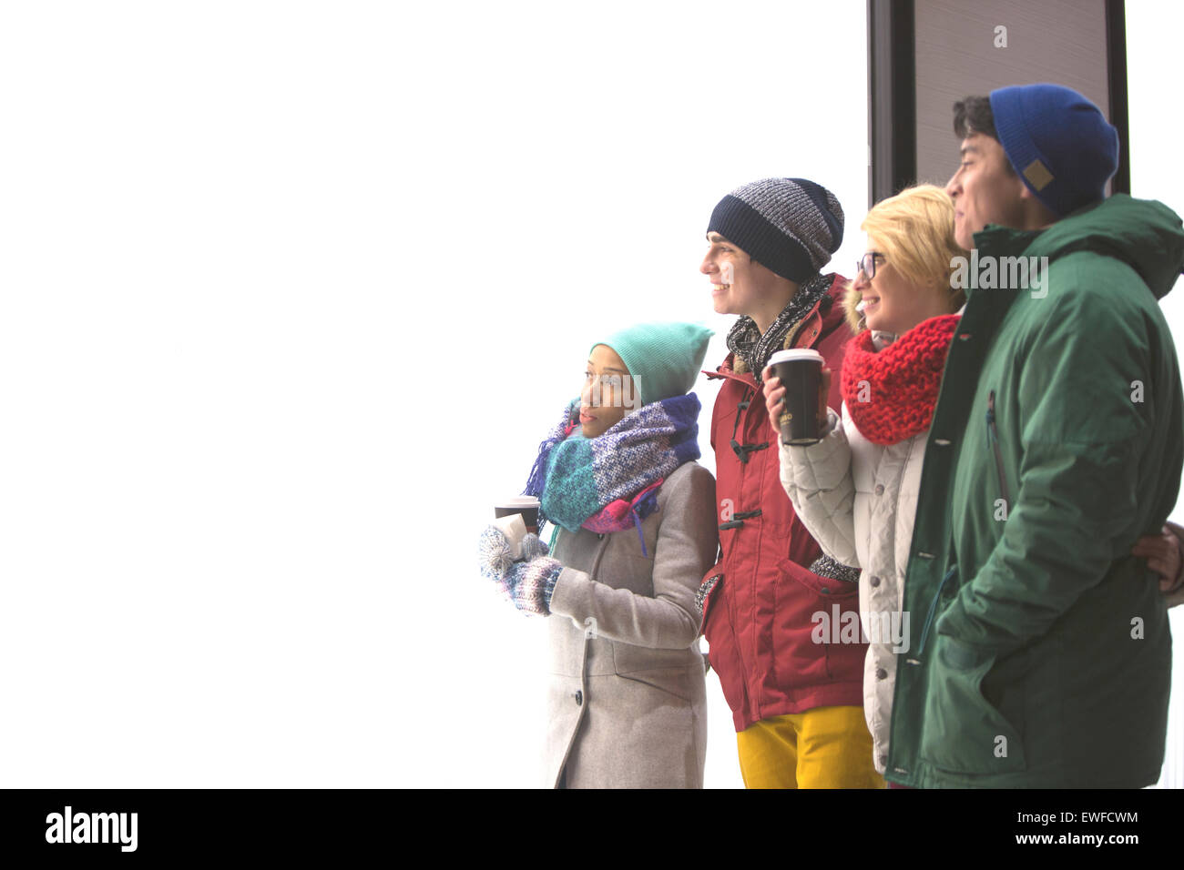 Multiethnic friends looking away against clear sky during winter - Stock Image