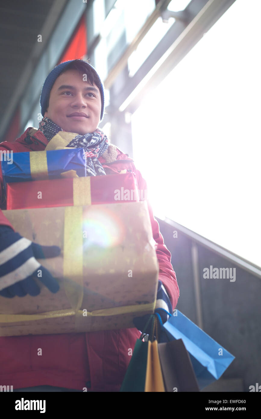 Low angle view of man holding gifts by window - Stock Image