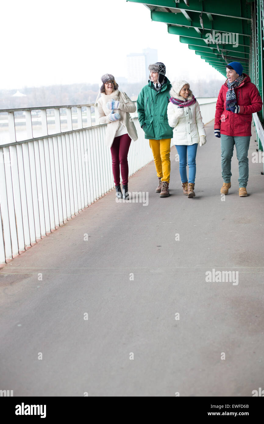 Multiethnic friends walking on footpath during winter - Stock Image
