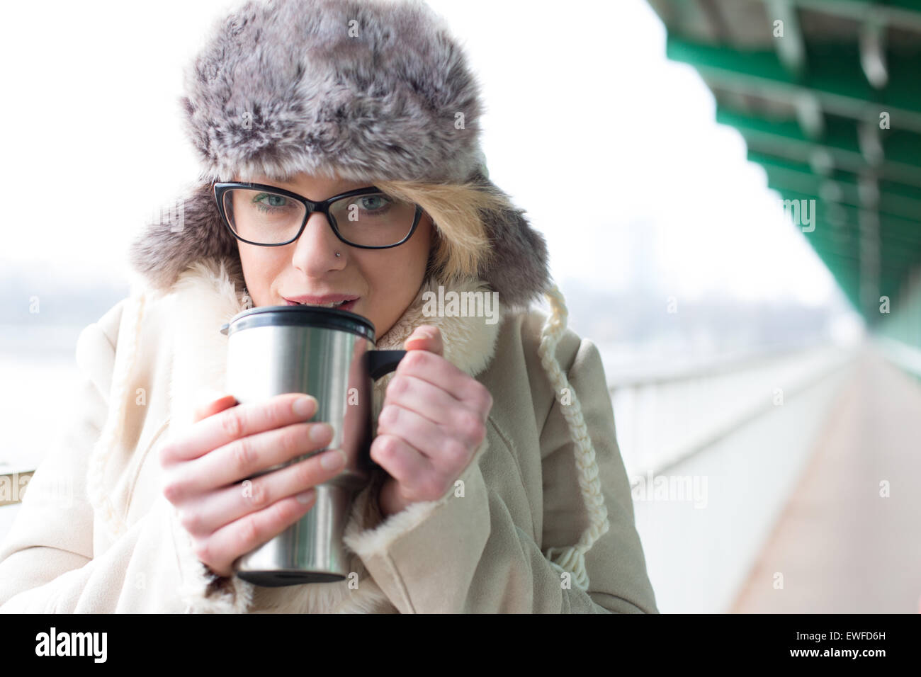 Portrait of woman drinking coffee from insulated drink container during winter - Stock Image