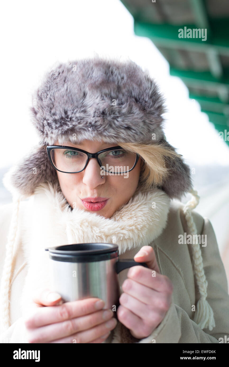 Portrait of woman blowing coffee in insulated drink container during winter - Stock Image