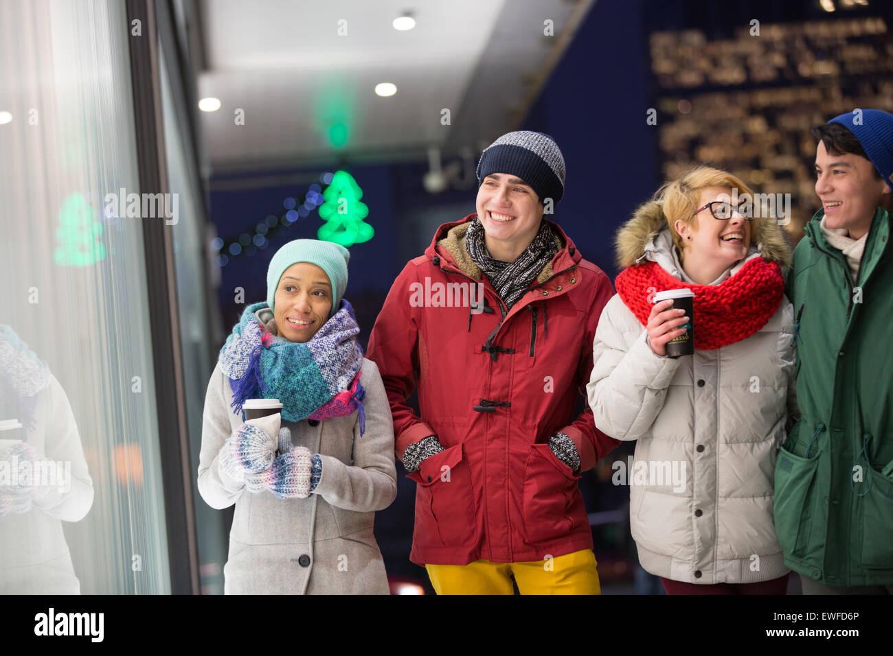 Happy multiethnic friends in winter wear walking in city during dusk - Stock Image
