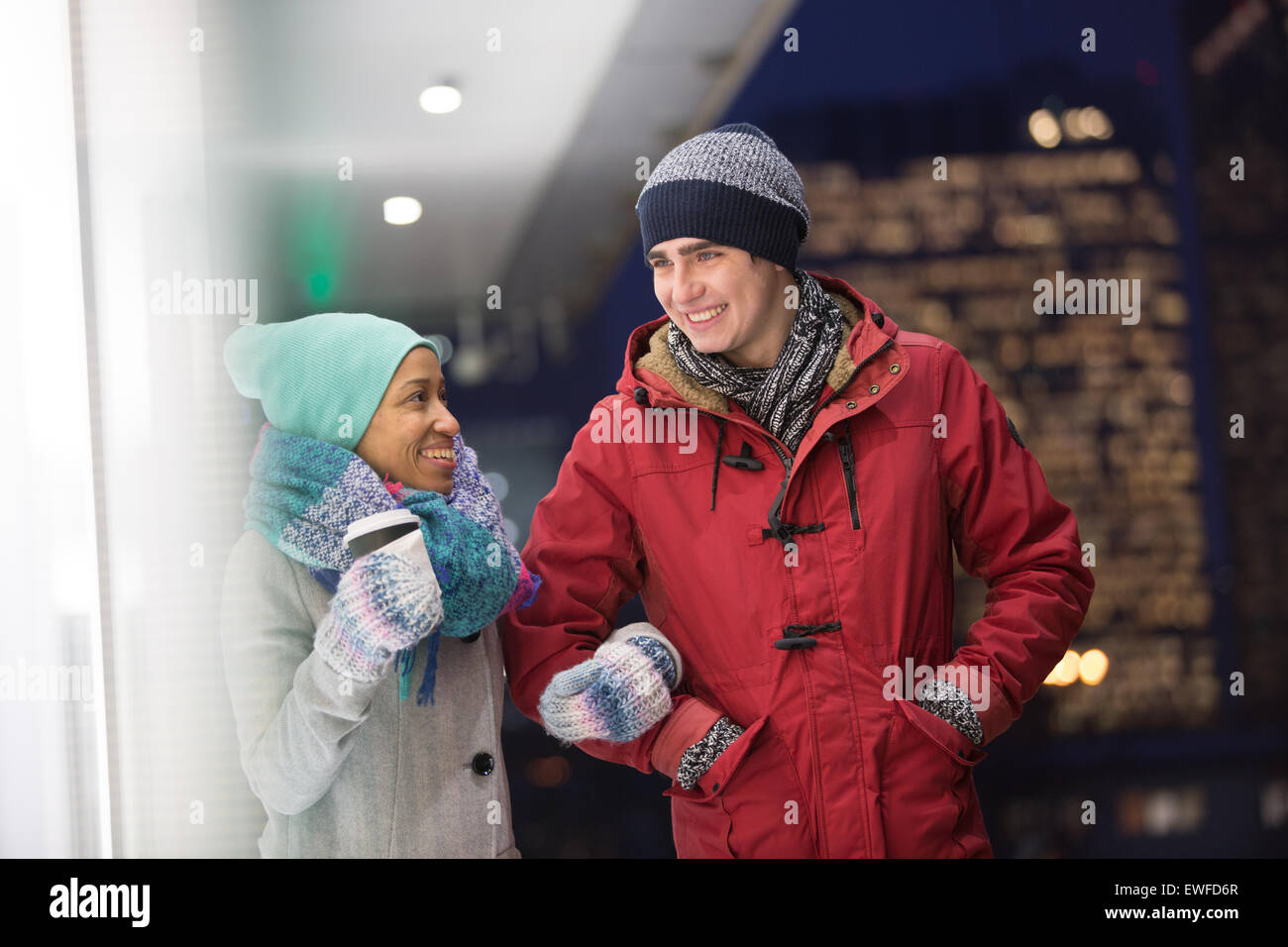 Multiethnic couple conversing at dusk during winter - Stock Image