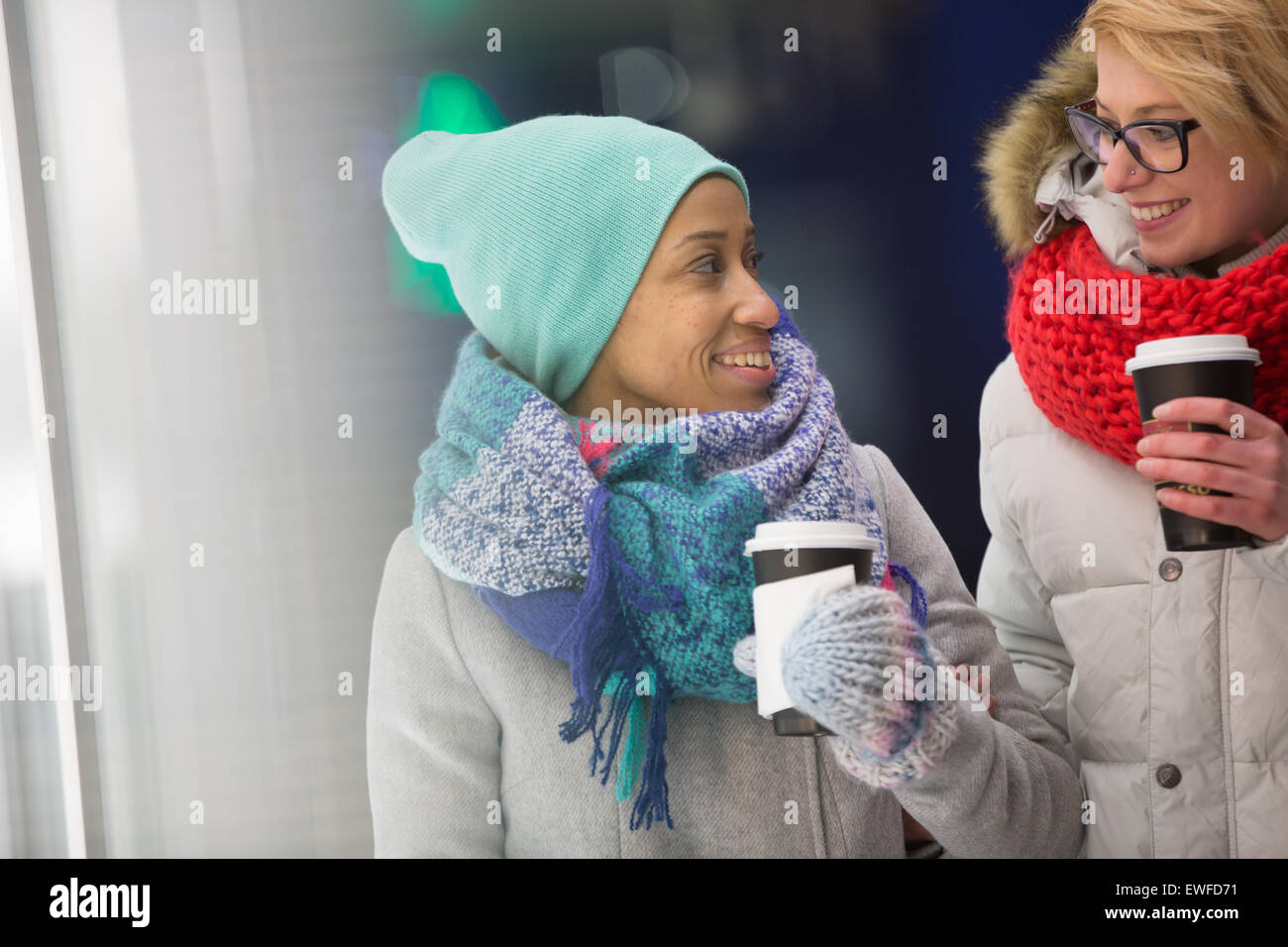 Happy women looking at each other while holding disposable cups - Stock Image
