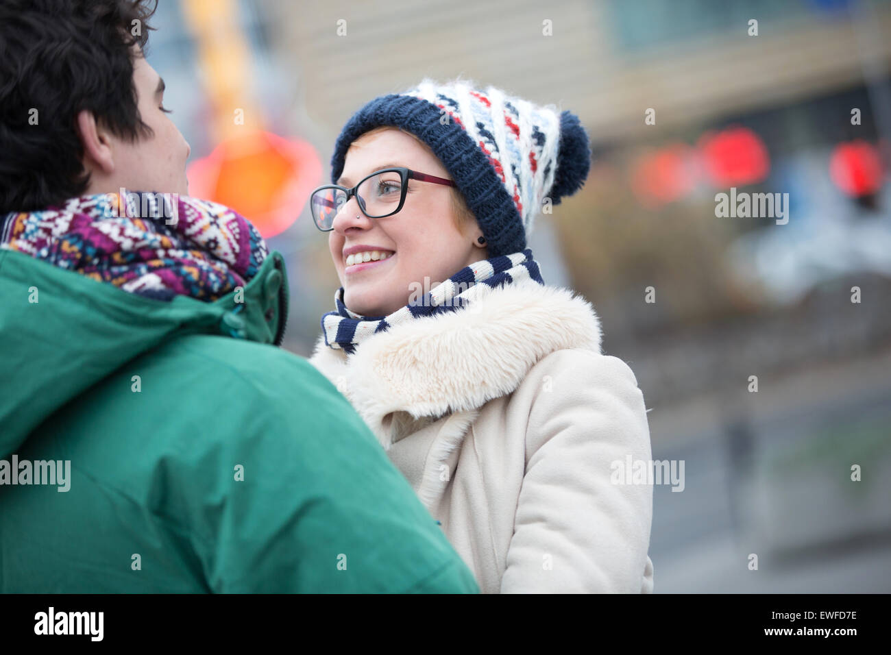 Romantic couple looking at each other in city during winter - Stock Image