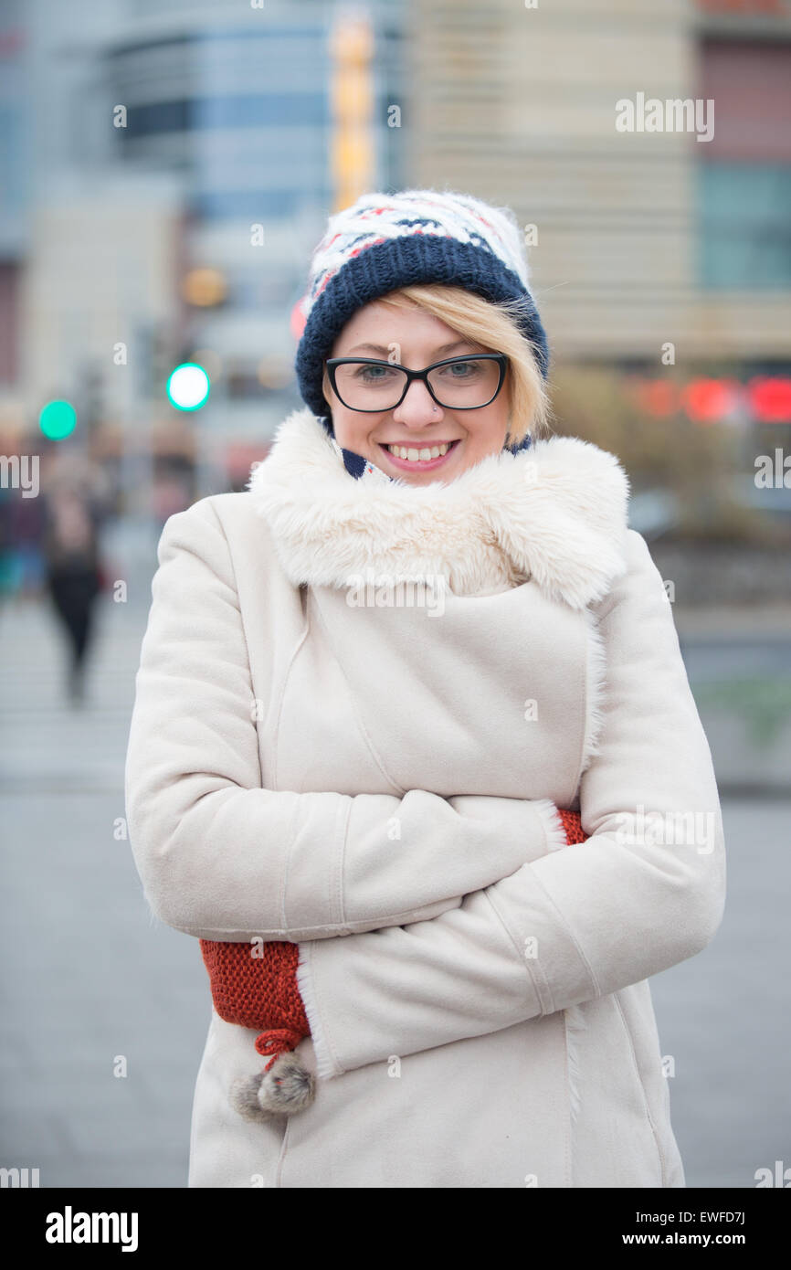 Portrait of happy woman in warm clothing standing arms crossed on city street - Stock Image