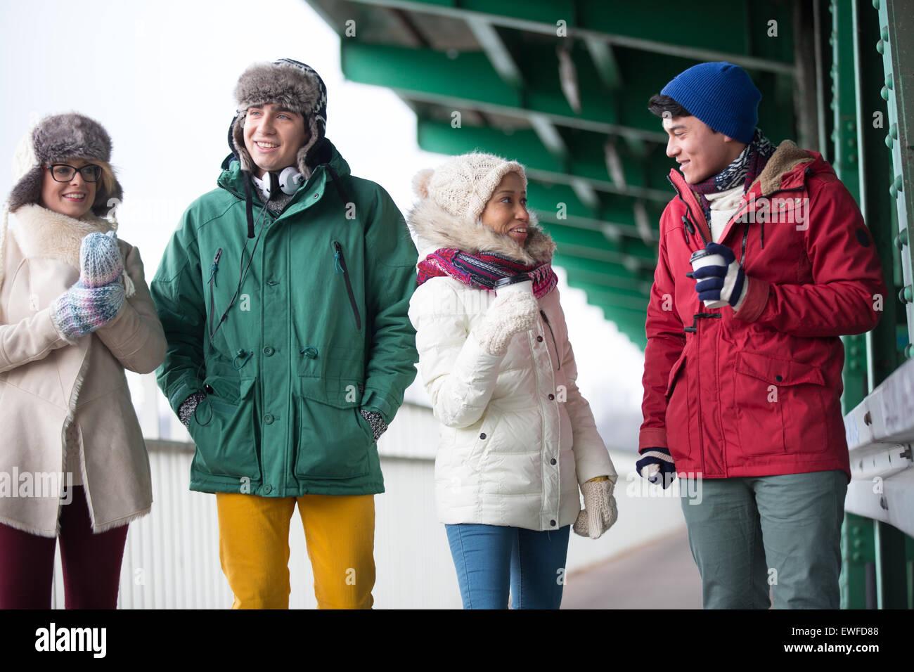 Multiethnic friends in winter wear conversing outdoors - Stock Image