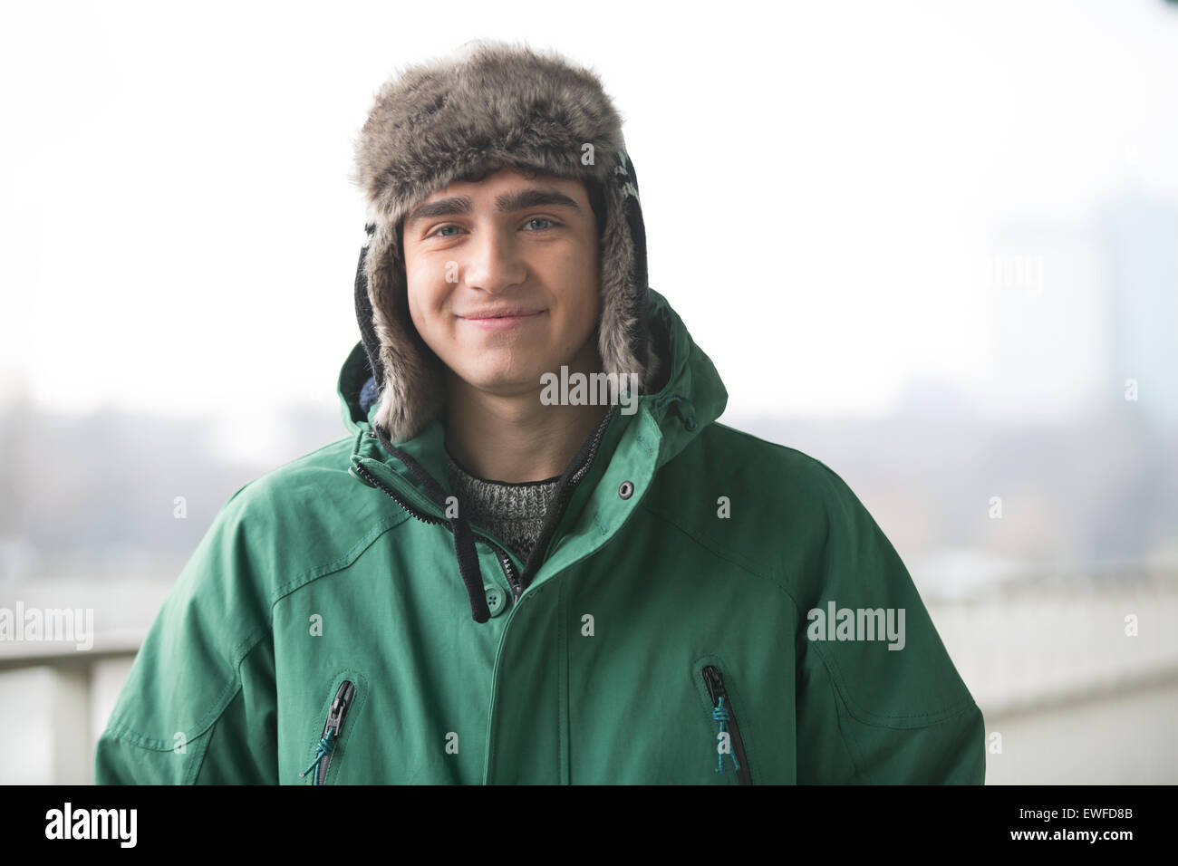 Portrait of man in winter wear smiling outdoors - Stock Image