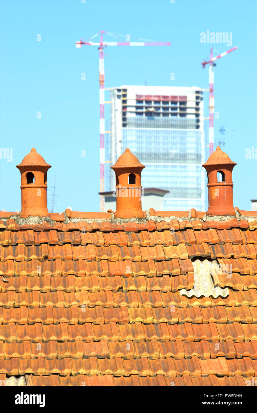 Three old chimney pot with modern construction in the background - Stock Image