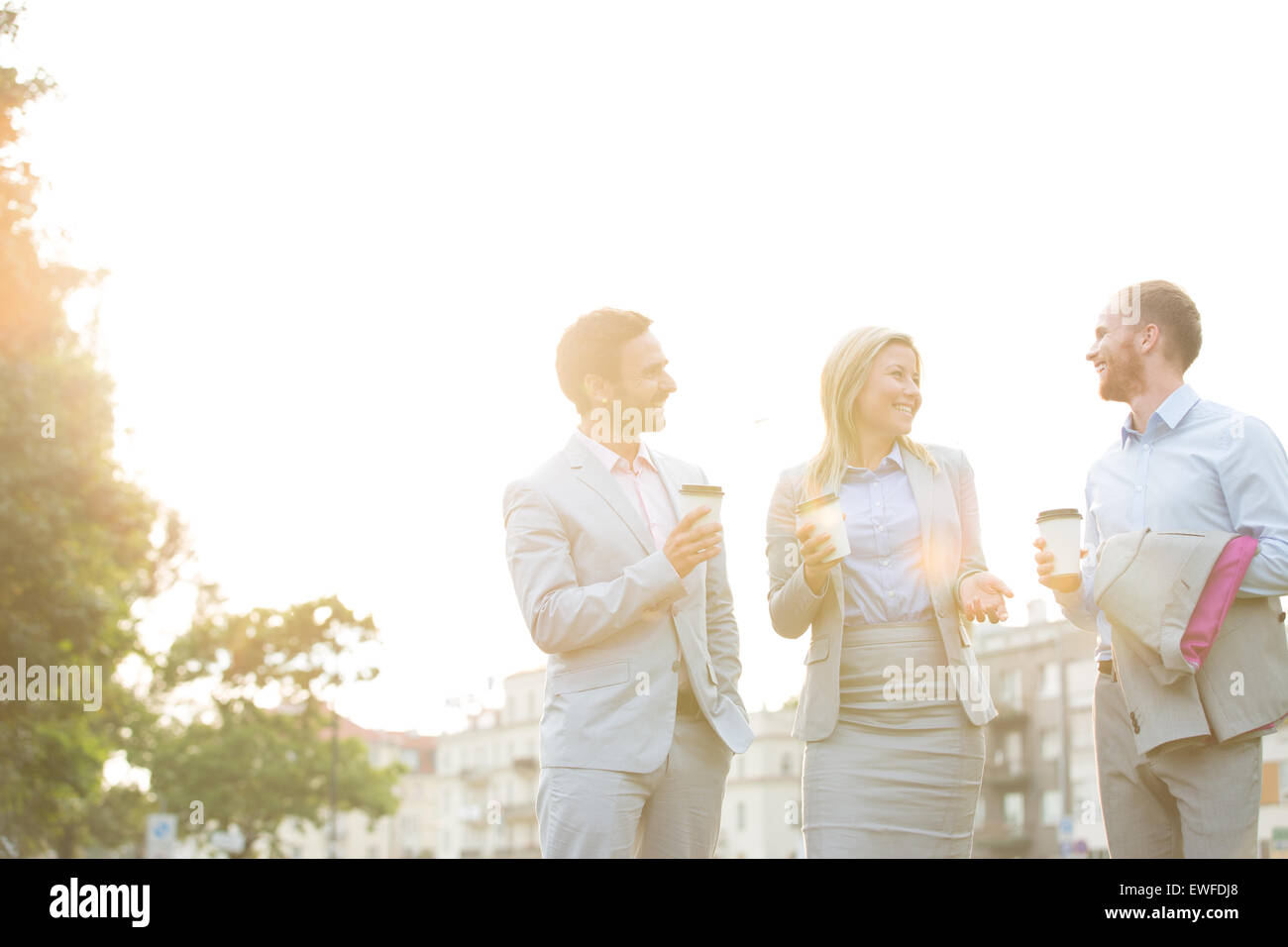 Happy businesspeople with disposable cups talking against clear sky on sunny day - Stock Image