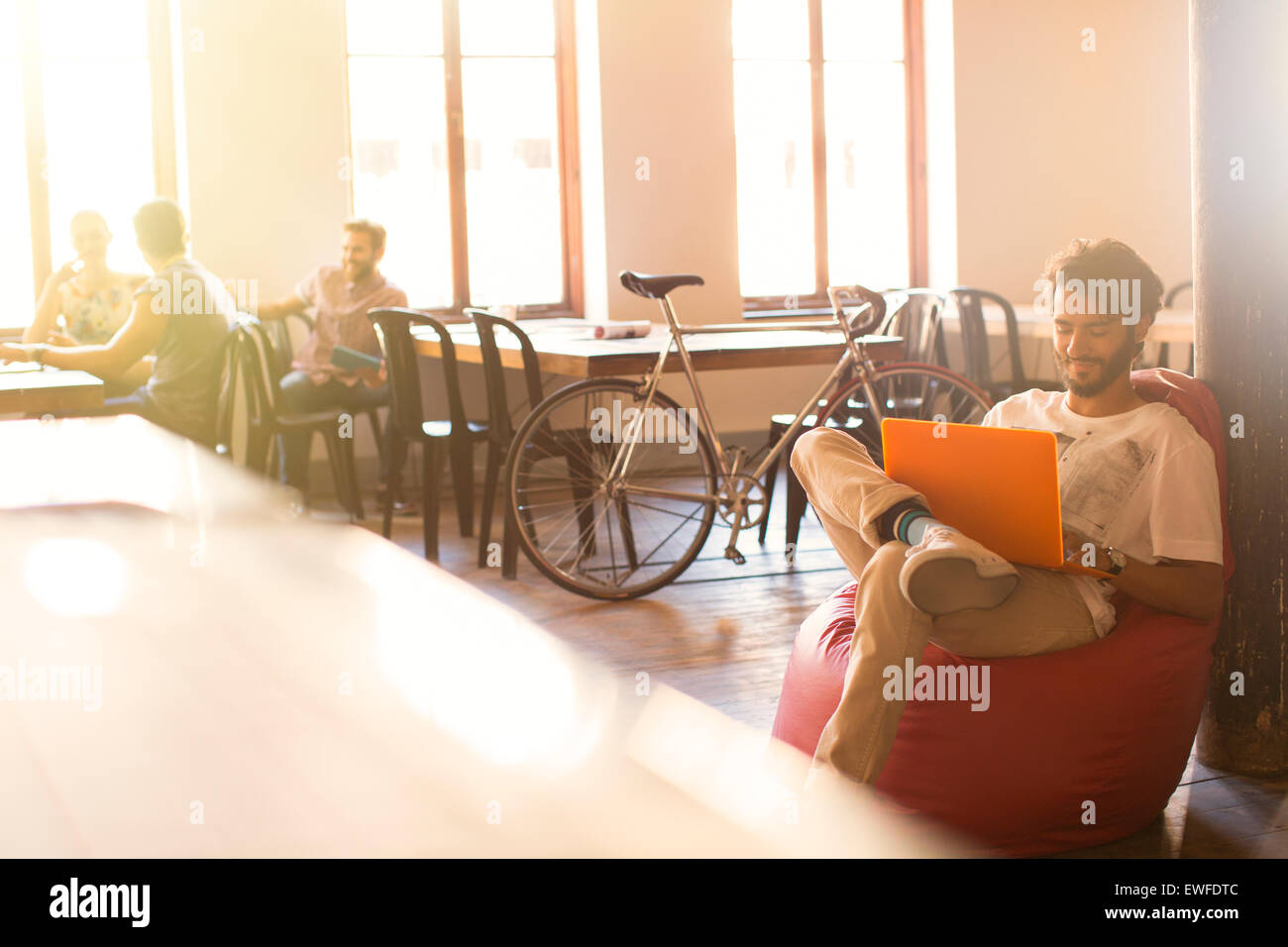 Casual businessman working at laptop in bean bag chair - Stock Image