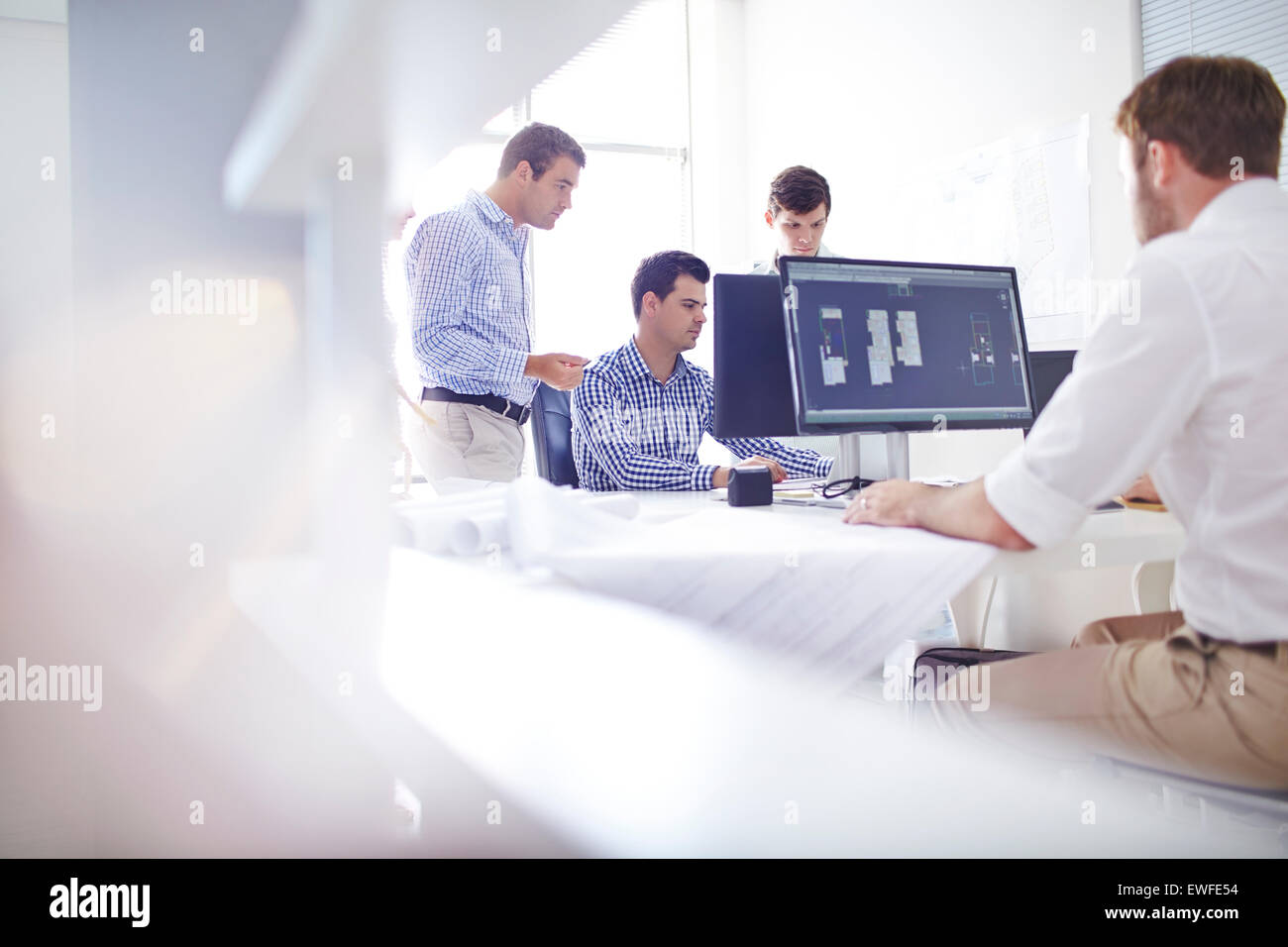 Architects drafting blueprints at computers in office - Stock Image