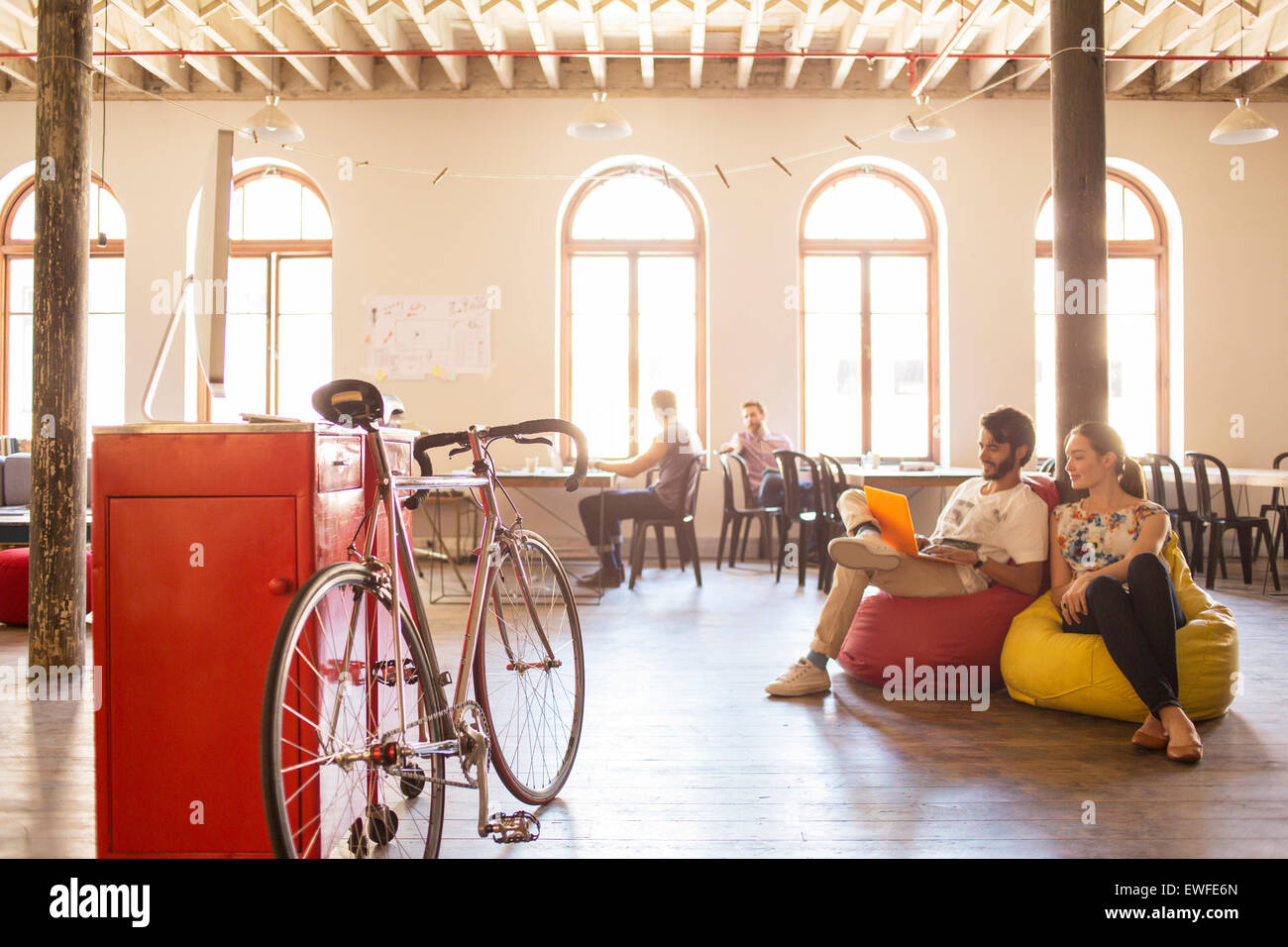 Creative business people using laptop on bean bag chairs in office - Stock Image
